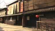 A red lantern hangs from the awning of a building in the Gion district of Kyoto.