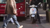 A red London bus and a scooter with an L plate and flashing indicator wait at traffic lights as pedestrians cross the road.