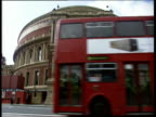 Red London bus drives past front of Royal Albert Hall