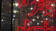 CU TD TU Red neon sign hanging in window of restaurant, people eating in background / Beijing, China