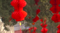 Red paper lanterns hang from trees in Beijing, China.