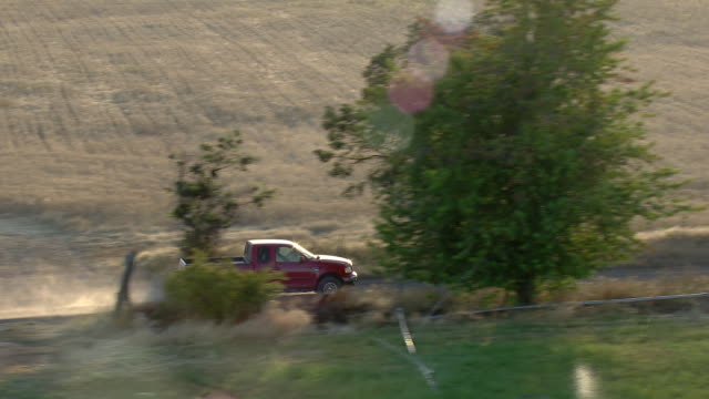 Red pickup truck driving a gravel road through fields and trees