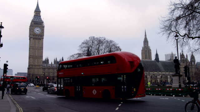 Red Routemaster Bus at Parliament square overlooking Big Ben and House of Parliament in slow motion