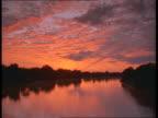 A red sky illuminates the Luangwa River.