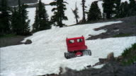 MS Red snow cat travelling away on snow covered mountain