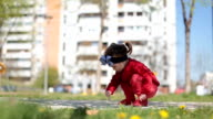 Red toddler girl playing in a park