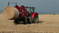 Red Tractor Harvesting Straw Bales