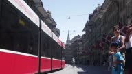 Red trams move past buildings and through the streets of the Swiss capital of Bern in Switzerland on Monday June 29 2015 Shots Pedestrians and...