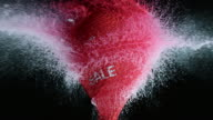 SLO MO red water filled balloon with sale sign exploding