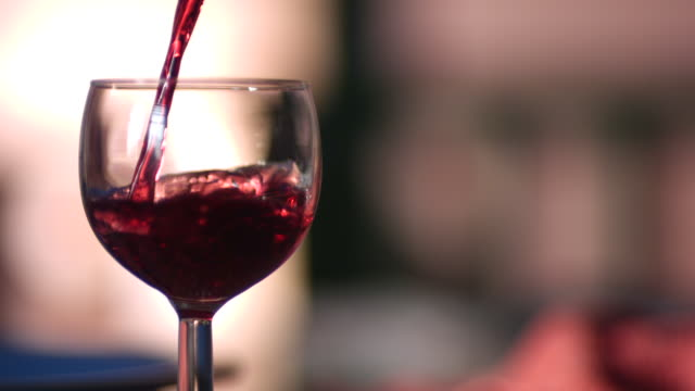 CU SLO MO Red wine being poured into wine glass from above / Manchester, United Kingdom