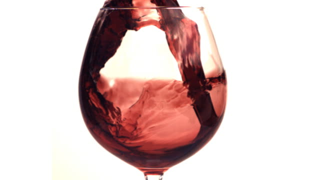 Red wine poured into a glass in slow motion. HD.