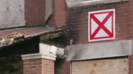 CU PAN red 'X' on facade of run-down apartment