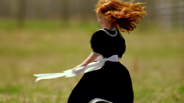 Redheaded girl in black dress smiling + spinning around in green field / Montana