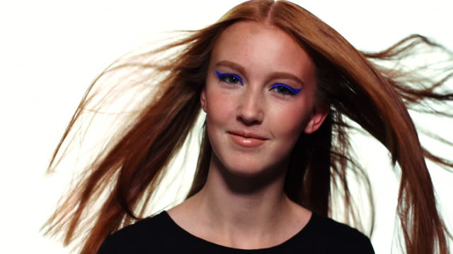 A redheaded girl looking into camera and smiling while her hair blows around her.