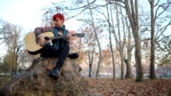 Redheaded Woman Playing Acoustic Guitar Sitting On a Tree Stump