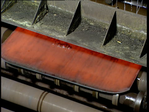 Red-hot sheet of newly-pressed steel emerging from rolling machine with water acting as coolant