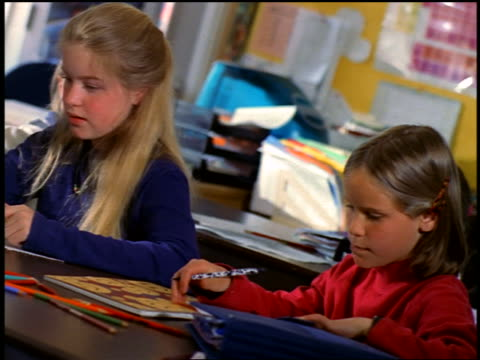 CANTED red-shirted girl whispering to blonde girl sitting next to her / blonde nodding / classroom.