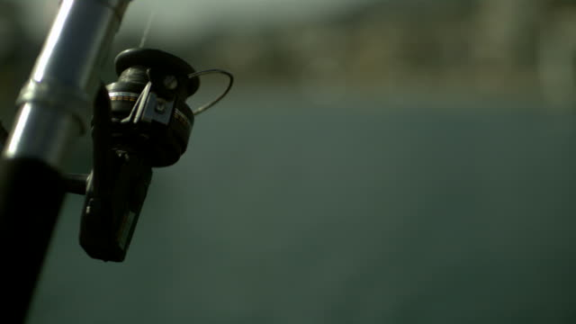 SLO MO reel of fishing rod, boat passes in background, Spain