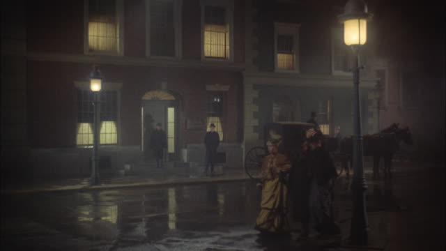 1966 WS Reenactment Horse carriages and people on wet, misty street at night