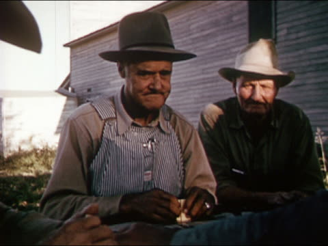 1963 Reenactment medium shot 19th century 'old timer' cowboys sitting at table playing dominos / man in overalls spitting tobacco / AUDIO
