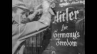 / Reenactment of Nazi Party members putting up banners and posters promoting Hitler and their party / montage of posters going up Nazis marching...