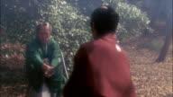 Reenactment wide shot rogue samurai swordfighting in forest / Japan