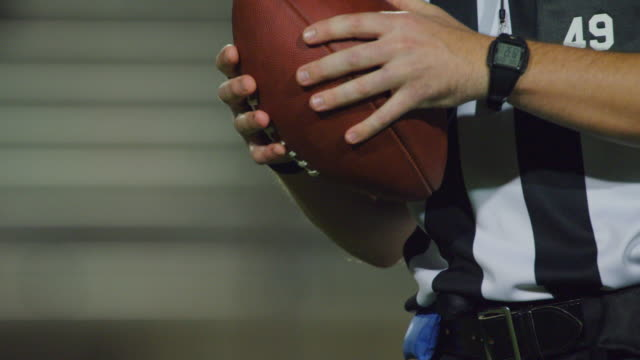 CU SLO MO. Referee grips football and throws an underhanded pass at camera.