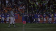 A referee picks up the place holder after a kickoff in a football game.