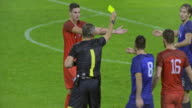 SLO MO Referee showing yellow card to player tackling opponent