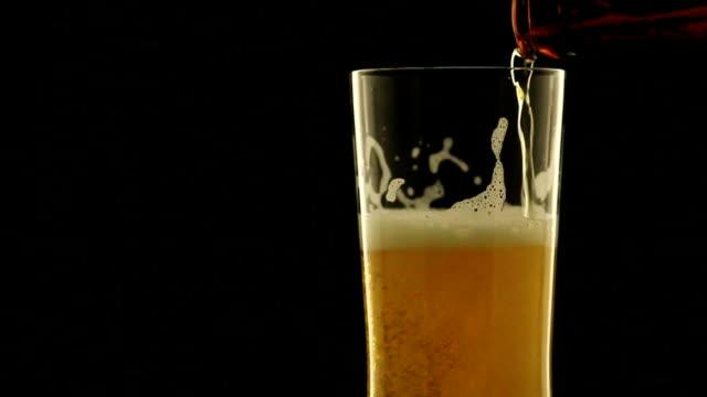 Drehen erfrischendes Bier in Glas in der dunklen Nacht