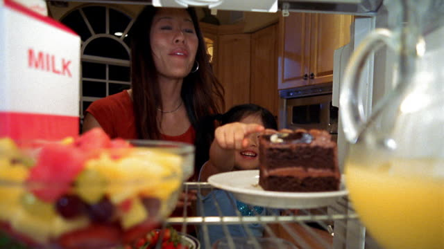 Refrigerator point of view Asian woman taking bowl of fruit from shelf and showing to young girl