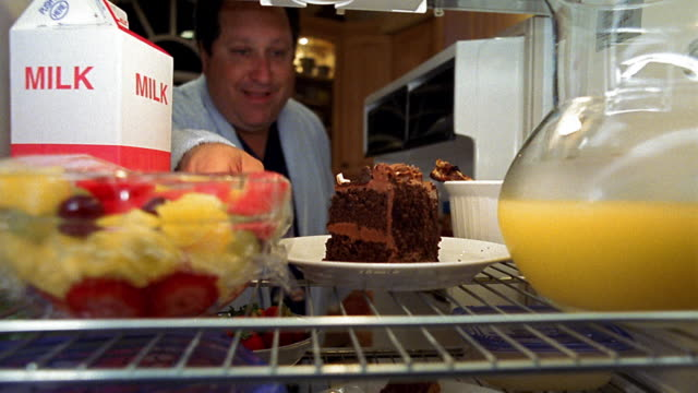 Refrigerator point of view man opening door and lifting piece of chocolate cake, but taking bowl of fruit