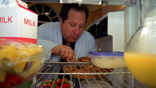 Refrigerator point of view man opening door, picking up tray of pie and eating with spoon / putting back pie