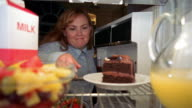 Refrigerator point of view woman opening door, looking at cake and taking bowl of fruit