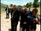 Refugees ITN Line of refugees crossing border from Kosovo Man helped along by others Men wiping their faces with cloths PAN Man near collapse helped...