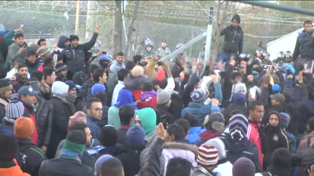 Refugees protest as they wait behind a fence to cross the border between Greece and Macedonia near the southern Macedonian town of Gevgelija on...