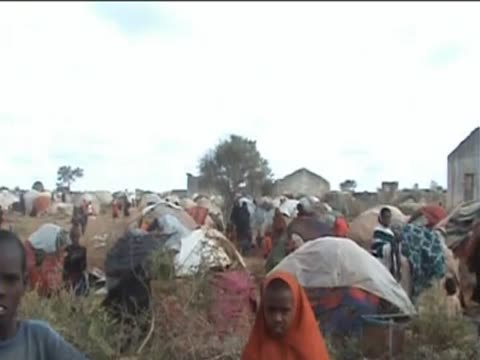 Refugees stand amongst tents at a refugee camp in Somalia during the drought and famine period August 2011