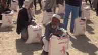 Refugees who have escaped from clashes in Taiz receive food aid distributed by a Qatari relief organization at garden of Mus'ab ibn 'Umair primary...
