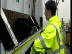 Refuse collector places glass bottles into recycling box on refuse lorry