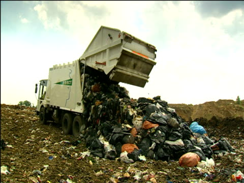 Refuse truck dumping rubbish into landfill moving forward to dump more