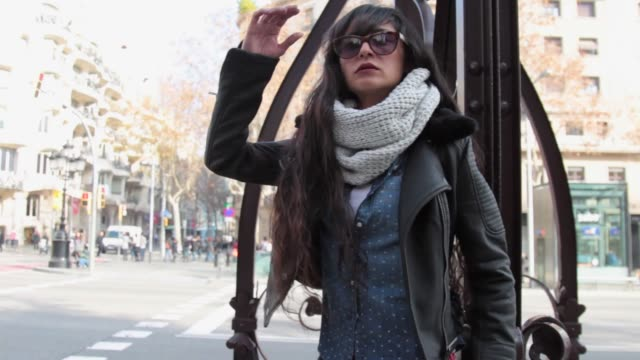 Regina is wearing a Superdry hat jacket scarf denim blouse shoes and handbag a Stradivarius white TShirt and Tous sunglasses in front of La Pedrera...