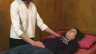 MS TD Reiki therapist touching woman lying on bed  / Manchester, Vermont, USA