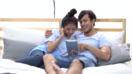 Relaxed asian young couple listen music and play social network by tablet on bed at home