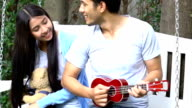 Relaxed asian young couple play guitar on white swing at home