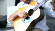 Ontspannen Aziatische jongeman gitaar spelen op bed thuis