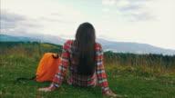 Entspannte schwangere Frau sitzen auf Rasen