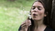 Relaxed woman in slow motion blowing a dandelion