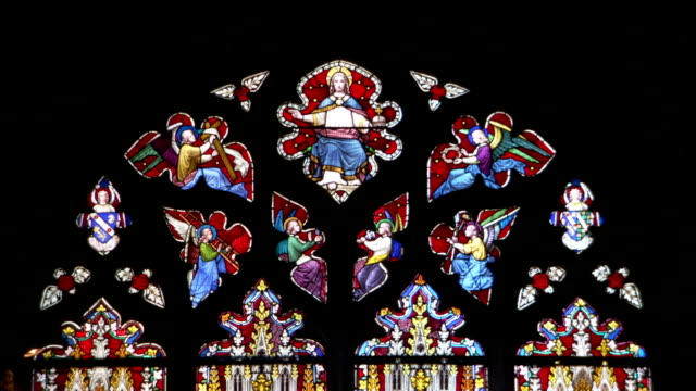 Religious figures decorate a stained glass window in England's Ely Cathedral. Available in HD.