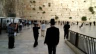 A religious man walks to the Wailing Wall and begins to pray