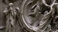 A religious scene of angels holding the body of Christ is sculpted in a wall of the Milan Cathedral. Available in HD.